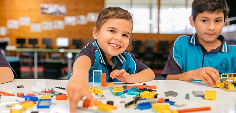 A primary school girl playing with lego.